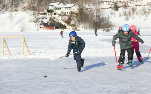 Ved hjelp av snøskuffer og vatn blei hockeybanane fullt brukelege. Her er det elevar frå andre klasse på Risvoll skule som kosar seg.