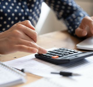 Woman using calculator counting finances calculate bills pay online, closeup